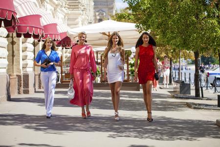 compras compulsivas: Retrato de una hermosa joven de cuatro mujeres de la moda a pie de la ciudad del verano