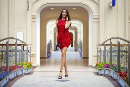 go inside: Beautiful young woman in red dress walking in the shop