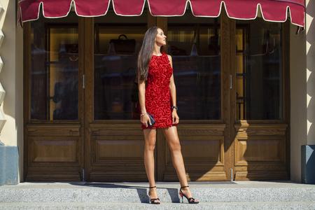 Joven y bella mujer de vestido rojo en la tienda Foto de archivo