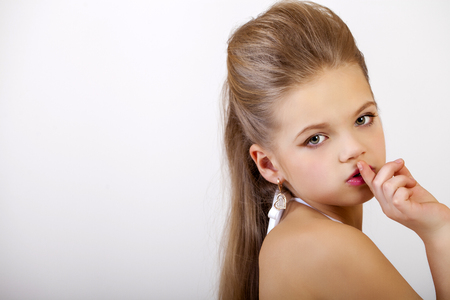 Young beautiful Little girl  has put forefinger to lips as sign of silence Stock Photo