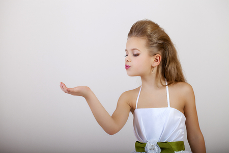 glamour makeup: Portrait of a little girl in white classic dress, isolated on gray background Stock Photo