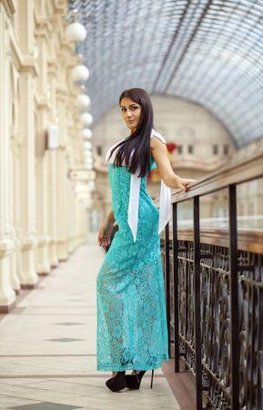 azerbaijani: Beautiful young arabic woman in long green dress in the shop