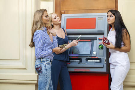 withdrawing: Three young beautiful modern girls using an automated teller machine. ATM, Women withdrawing money or checking account balance