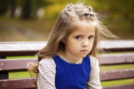 petite fille triste: Petite fille triste est assis sur le banc, automne tournage en plein air Banque d'images
