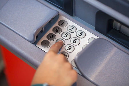personal identification number: Female arms, ATM - entering pin Stock Photo