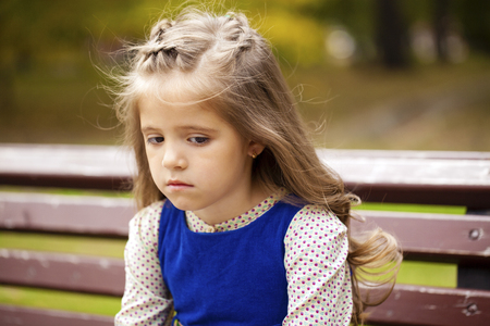 petite fille triste: Sad little girl is sitting on the bench, autumn outdoor shoot