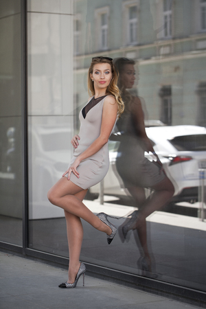 short dress: Portrait in full growth, Young beautiful blonde woman in beige short dress posing against a background of a wall mirror