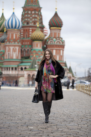 red square: Portrait in full growth, Russian beautiful woman in a mink coat on the Red Square in Moscow