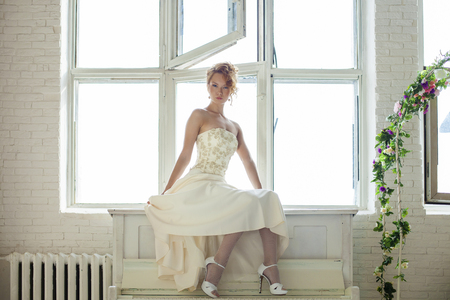 Charming beautiful young red hair girl in a white lace dress sits on the window in the interiors of the house