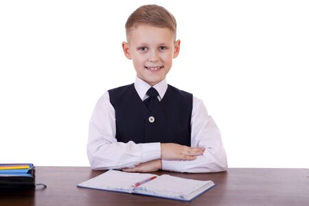 bored student: Caucasian school boy at his desk on white background with copy space - bored student boy reading book or textbook