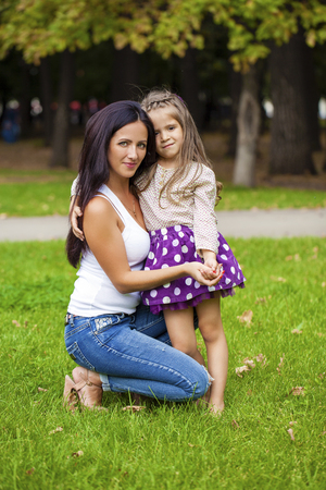 nine year old: portrait of a beautiful nine year old little girl and happy mother in autumn park
