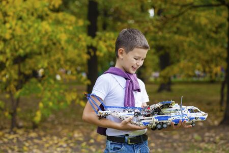 7 9 years: Portrait of a pretty brunette little Boy holds plastic model airplane in autumn park