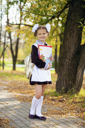 7 9 years: Portrait of a beautiful young first-grader in a festive school uniform on the background autumn park Stock Photo