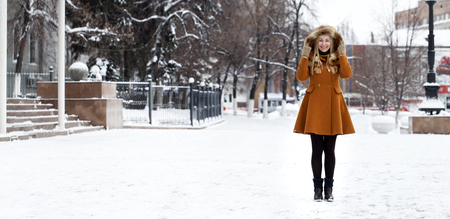 Portrait in full growth of a beautiful young blonde woman on the background of a winter street Stock Photo