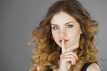 forefinger: Young beautiful haired woman has put forefinger to lips as sign of silence