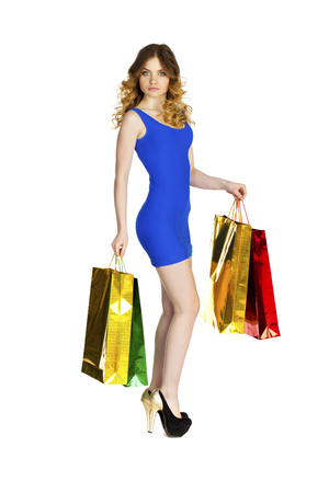 blue dress: Full portrait of smiling young blonde girl with colorful shopping bags in blue dress posing on a white background