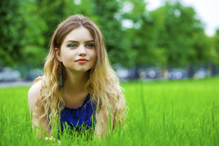 Sexy young blonde woman in white dress sitting on green grass in summer park