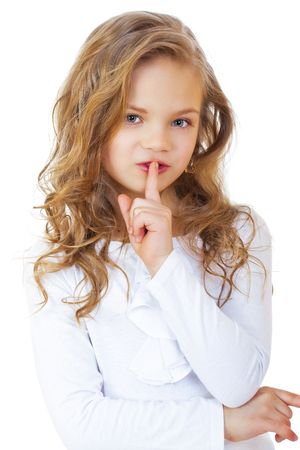 silencio: Joven hermosa niña ha puesto el dedo índice a los labios en señal de silencio