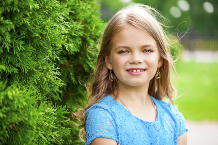Portrait of beautiful little girl, against background of summer park Stock Photo