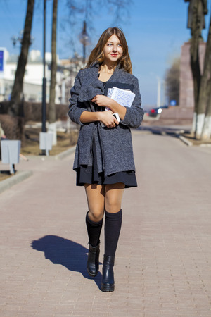 sixteen year old: Young beautiful girl in a gray coat walking down the street