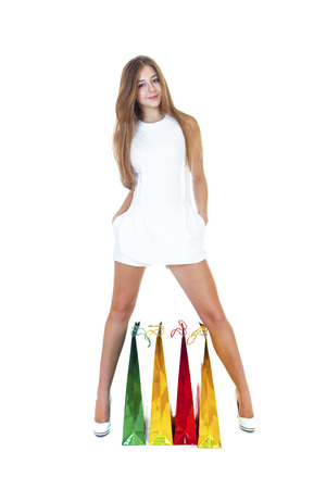16 years: Full portrait of smiling young blonde girl with colorful shopping bags in white dress posing on a white background Stock Photo