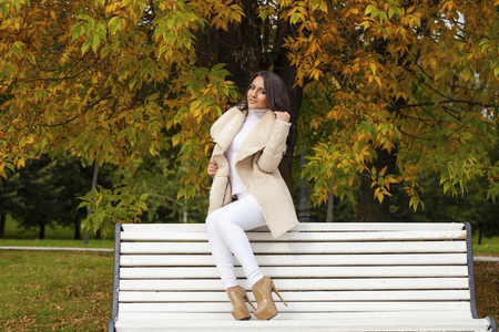 Young beautiful arabic brunette women in white sheepskin coat sitting on a bench in the autumn park
