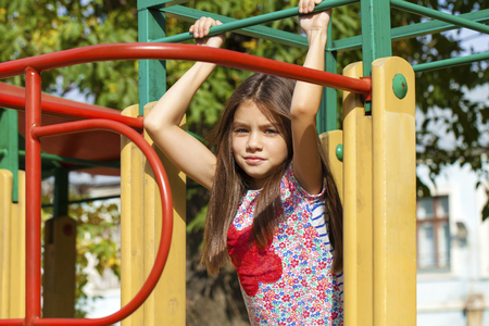 8 10 years: Cose up, Beautiful little girl on green background of summer city park
