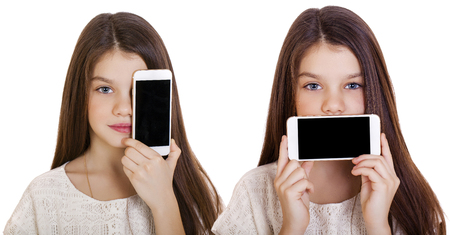 10 12 years: Happy little girl covers her face screen smartphone on white isolated background