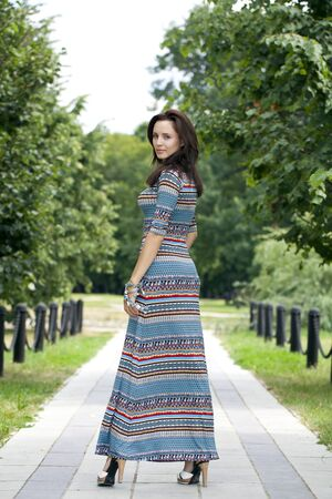 colorful dress: Beautiful young woman in colorful dress, against green of summer park