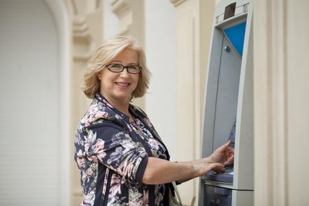 automated teller machine: Mature blonde woman counting money near automated teller machine in shop