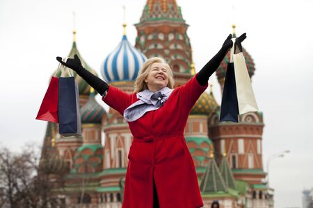age 60: Mature happy blonde woman with shopping bags on Red Square in Moscow