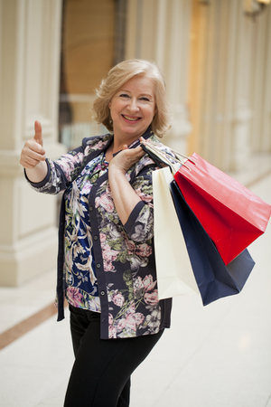 age 60: Mature happy blonde woman with shopping bags