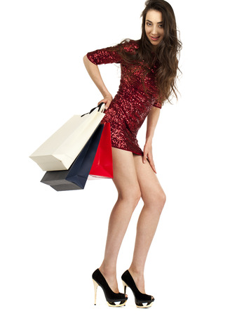 25 30 years: Fashion woman portrait isolated. White background. Happy girl hold shopping bags. Red dress. female beautiful model
