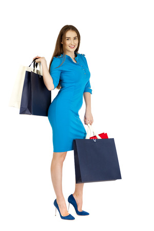 25 30 years women: Fashion woman portrait isolated. White background. Happy girl hold shopping bags. Blue dress. female beautiful model