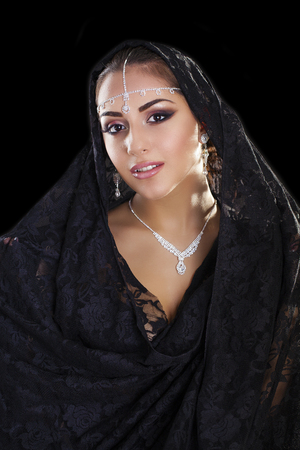 yashmak: Portrait of a beautiful woman with arabian makeup in black paranja isolated on dark background Stock Photo