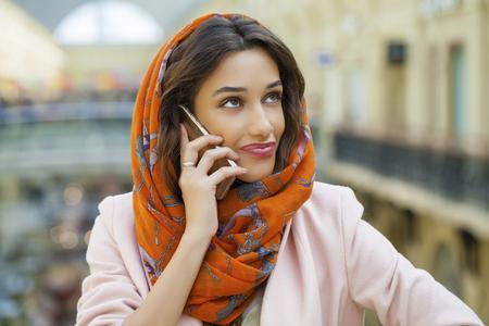 identidad cultural: Cerca de retrato de una joven musulmana con pa�uelo en la cabeza una llamada por tel�fono