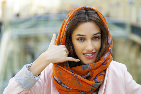 call me: Beautiful brunette woman making a call me gesture. Arab young girl in orange scarf