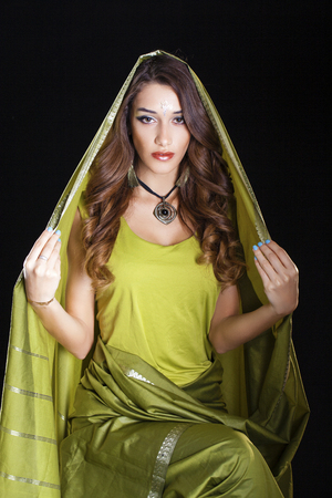 arab glamour: Young beautiful brunette woman in gree indian dress, isolated on black background