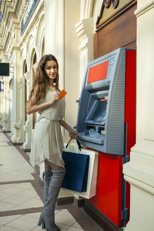 automated teller machine: Brunette young lady using an automated teller machine .