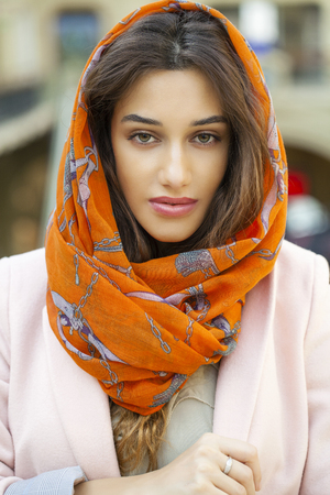 head scarf: Close up portrait of a muslim young woman wearing a head scarf, indoor