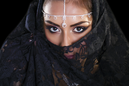 paranja: Portrait of a beautiful woman with arabian makeup in black paranja isolated on dark background Stock Photo