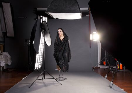 studio model: Working conditions in the studio, the photographer photographs the professional model, dark photo studio