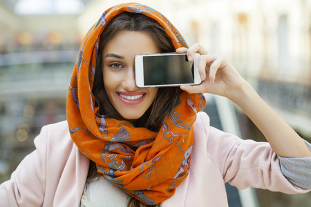 head scarf: Phone display. Close up portrait of a muslim young woman wearing a head scarf, indoor