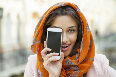 identidad cultural: Phone display. Close up portrait of a muslim young woman wearing a head scarf, indoor