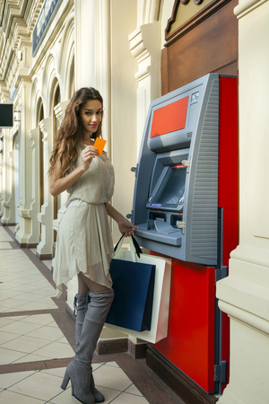 cash dispenser: Brunette young lady using an automated teller machine . Woman withdrawing money or checking account balance Stock Photo