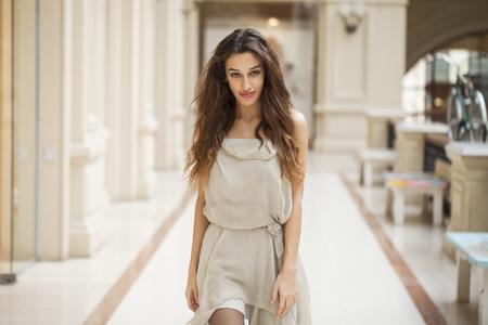 armenian woman: Portrait close up of young beautiful brunette woman in beige dress walkin in the shop