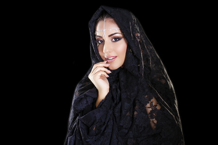 ojos negros: Retrato de una mujer hermosa con maquillaje árabe en paranja negro aislado en el fondo oscuro