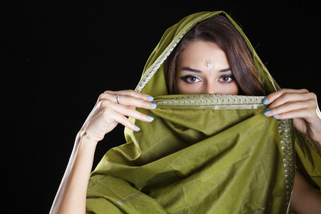 gree: Young beautiful brunette woman in gree indian dress, isolated on black background