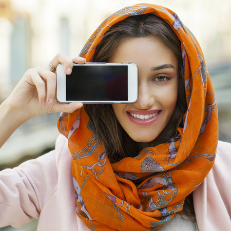 identidad cultural: pantalla del teléfono. Cerca de retrato de una joven musulmana que llevaba un pañuelo en la cabeza, cubierta