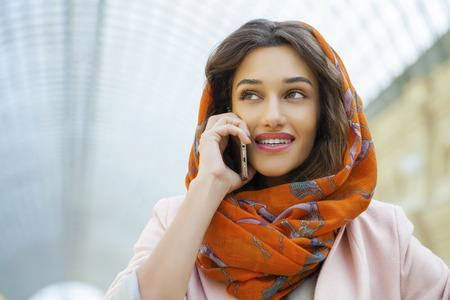 identidad cultural: Cerca de retrato de una joven musulmana con pañuelo en la cabeza una llamada por teléfono